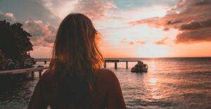 woman wearing bikini facing the sunset